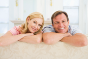 Insurance policy holder couple smiling on couch.