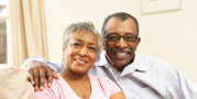 Insurance policy holder senior couple smiling on couch.